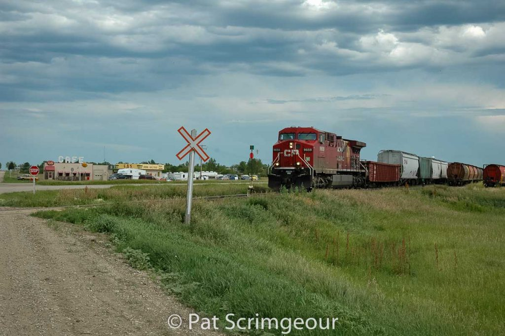 """CP 9659 passes the Corner Gas station in """"Dog River"""", SK, July 2005. Contributed by Pat Scrimgeour."""
