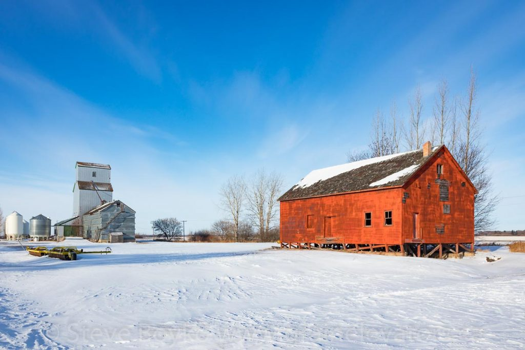 Flat grain warehouse and elevator in Brookdale, MB, Dec 2017. Contributed by Steve Boyko.