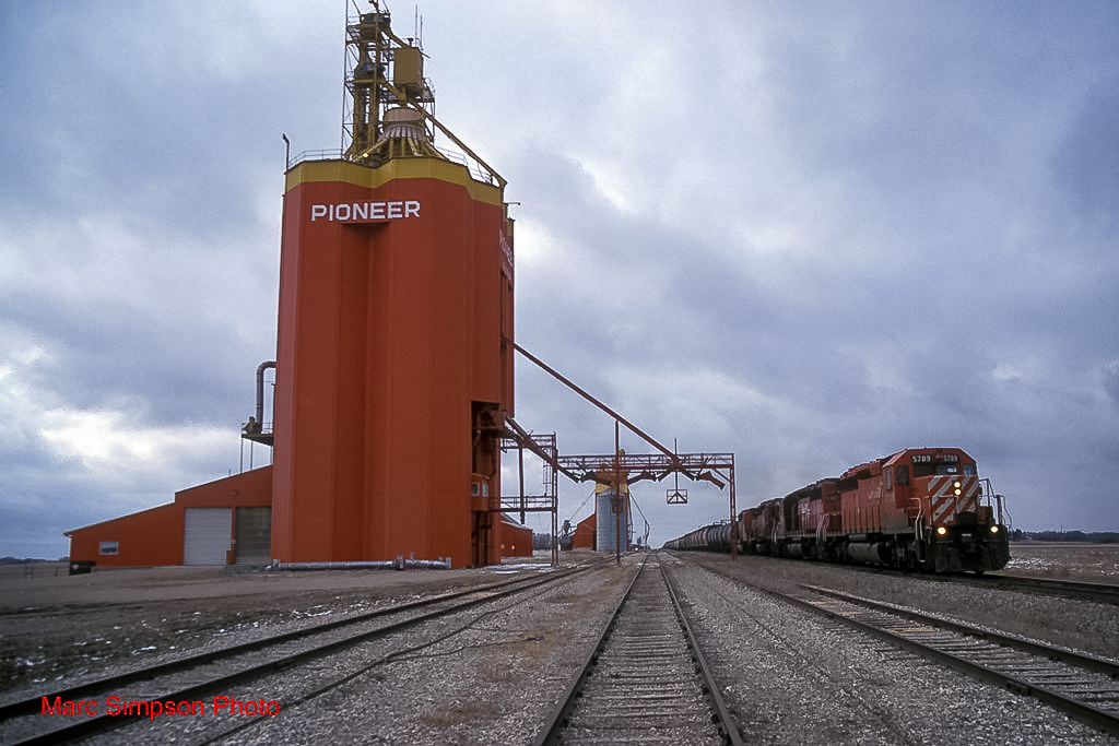 CP 5789 passes the Glossop, MB grain elevator, 1998. Copyright by Marc Simpson.
