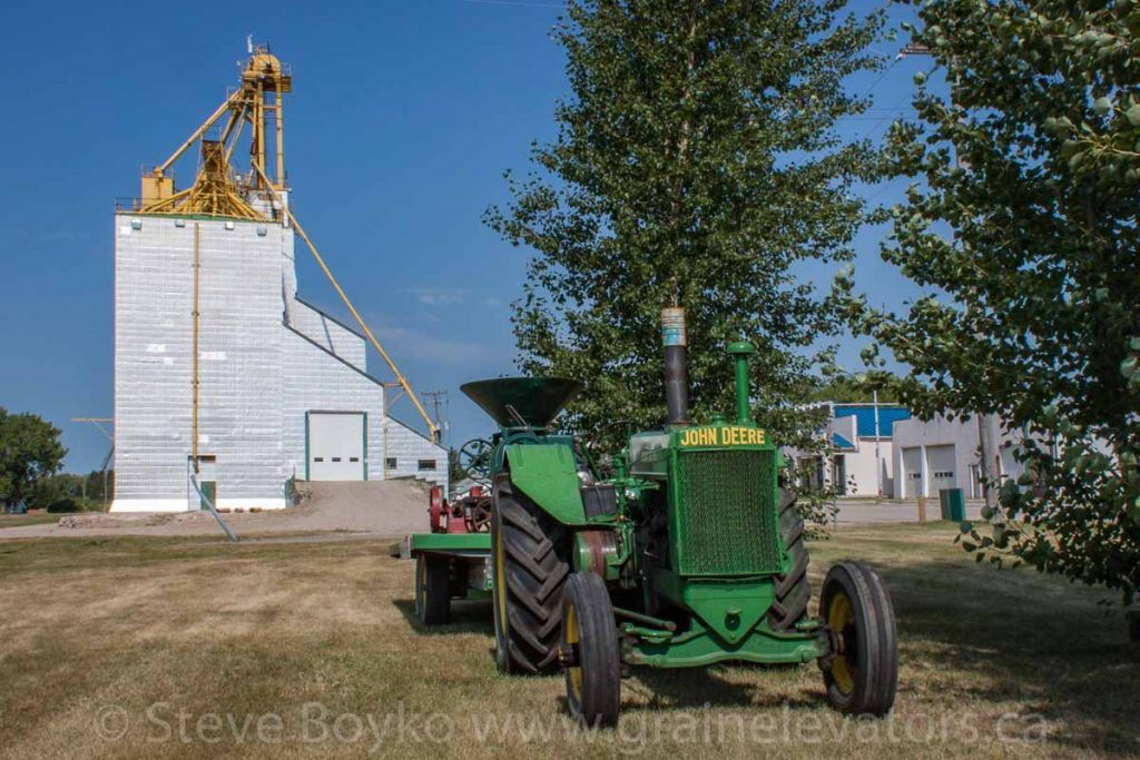 Tractor and grain elevator, Cartwright, MB, Aug 2014. Contributed by Steve Boyko.