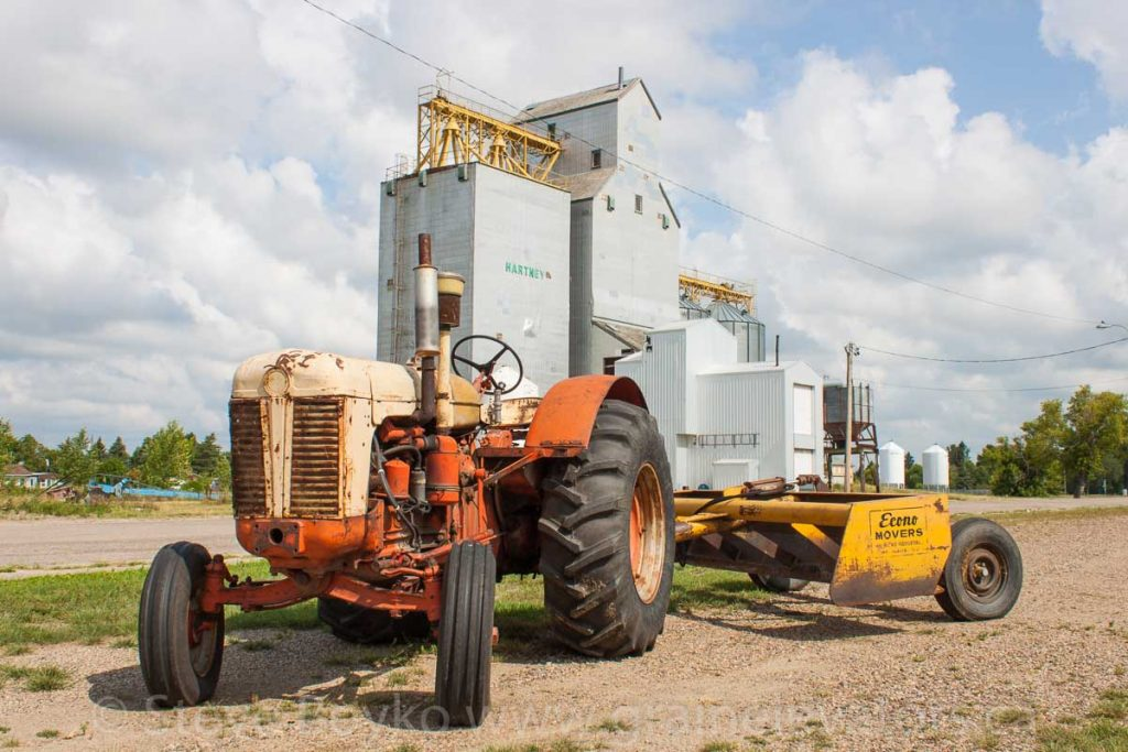 Tractor and grain elevator in Hartney, MB, Aug 2014. Contributed by Steve Boyko.