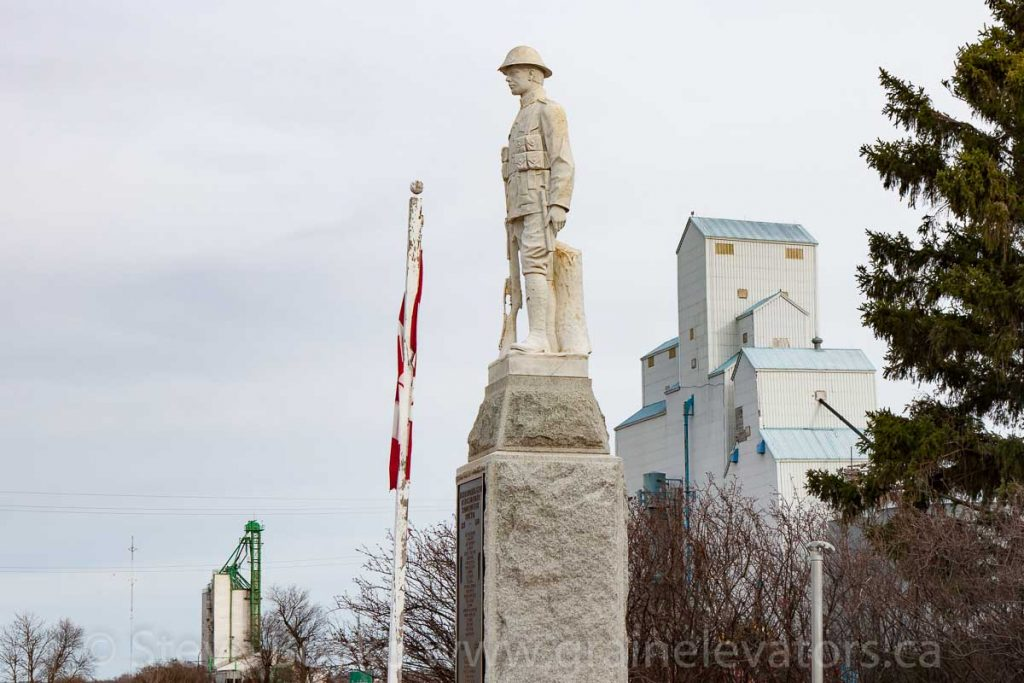 Statue and grain elevators in Newdale, Manitoba, Apr 2017. Contributed by Steve Boyko.